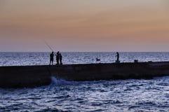有家庭协助的蓝色小时钓鱼者 库存照片
