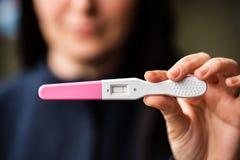 有家庭妊娠试验的哀伤的妇女 免版税库存图片