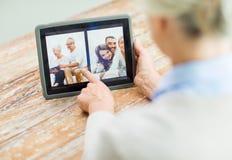 有家庭照片的资深妇女在片剂个人计算机屏幕上 免版税库存图片