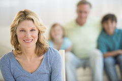 有家庭的妇女在家坐沙发在背景中 免版税库存图片