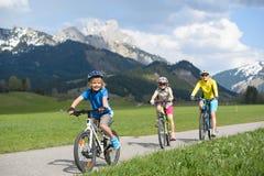 有家庭的微笑的小男孩骑马自行车 免版税图库摄影