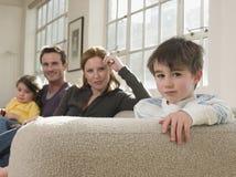 有家庭的逗人喜爱的男孩坐沙发 免版税库存照片