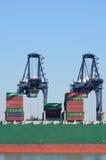 有容器的两台大装货起重机在小船 免版税库存照片