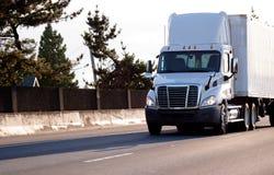 有容器的白色现代半卡车在的货物载体的 库存图片