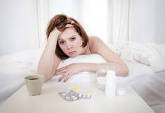 有宿酒的红发女孩在床上的想要咖啡 免版税库存照片