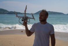 有寄生虫照相机的愉快的人在他的在海滩的手上 库存图片