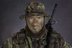 有密林伪装油漆的年轻战士 免版税库存照片