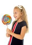 有对巨大螺旋棒棒糖糖果微笑负的长的金发的美丽的女孩愉快 库存图片