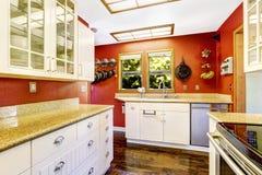 有对比明亮的红色墙壁的白色厨房室 库存照片