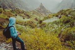 有寻找农村风景的动机与山峰和山沟的背包的旅客在道路的尘土空气从 库存图片