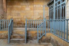 有导致砖石墙、木蓝色更衣室的楼梯栏杆和门的楼梯的被放弃的传统公共浴室 免版税库存照片
