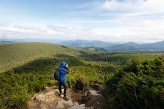 有射击室外意想不到的山风景的dslr照相机的年轻专业旅行家人 远足者在岩石站立 库存照片