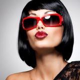 有射击发型的美丽的深色的妇女与红色太阳镜 免版税库存照片