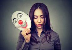 有小丑面具的哀伤的妇女 免版税图库摄影