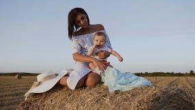 有小儿子的一个美丽的女孩在领域坐干草堆和使用与他 蓝色的可爱的少妇 影视素材