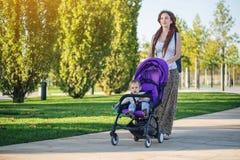 有小儿子的年轻现代妈妈走在晴朗的公园的婴儿推车的 母性和秋天心情喜悦的概念  库存照片