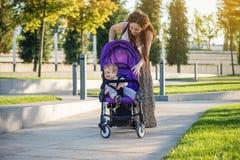有小儿子的年轻现代母亲走在晴朗的公园的婴儿推车的 母性和秋天心情喜悦的概念  库存照片