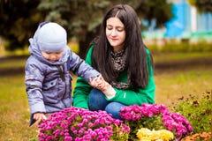 有小儿子的母亲充当秋天公园 库存图片