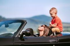 有小儿子的母亲在敞蓬车汽车坐 库存图片