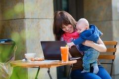 有小儿子的年轻工作母亲咖啡馆的 库存照片