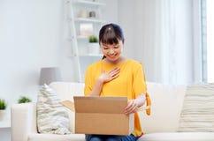 有小包的愉快的亚裔少妇在家装箱 库存照片