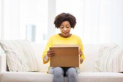 有小包的愉快的非洲少妇在家装箱 库存图片