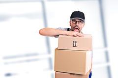 有小包的过度紧张的邮差 免版税库存照片