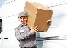 有小包的邮差在送货卡车附近 免版税库存图片