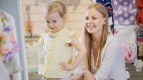 有小女儿买的孩子的白肤金发的妇女礼服在衣裳商店 库存图片