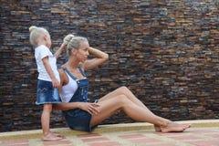 有小女儿开会和使用的年轻母亲 库存图片