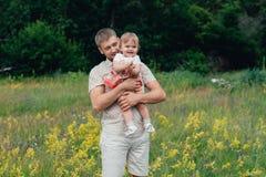 有小女儿的在公园,夏天愉快的父亲户外 免版税库存照片