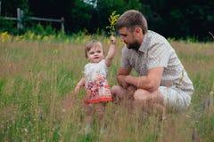 有小女儿的在公园,夏天愉快的父亲户外 库存图片