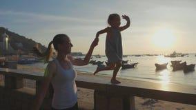 有小女儿的年轻母亲在慢动作的沿海岸区跑 股票录像