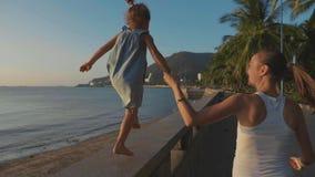有小女儿的年轻母亲在慢动作的沿海岸区跑 股票视频