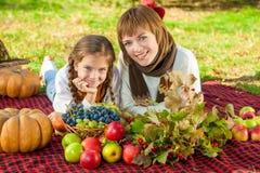 有小女儿的愉快的母亲在秋天公园 库存照片