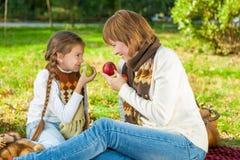 有小女儿的愉快的母亲在秋天公园 库存图片