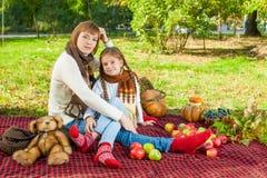 有小女儿的愉快的母亲在秋天公园 免版税库存照片