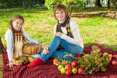 有小女儿的愉快的母亲在秋天公园 免版税图库摄影