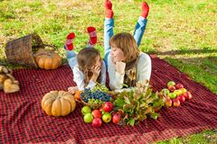 有小女儿的愉快的母亲在秋天公园 免版税库存图片