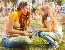 有小女儿的愉快的母亲holi颜色节日的 库存照片
