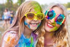 有小女儿的愉快的母亲holi颜色节日的 免版税库存图片