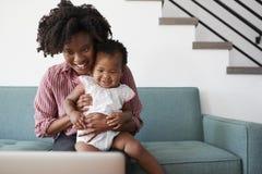 有小女儿的母亲在家坐看便携式计算机的沙发 免版税库存照片