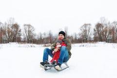 有小女儿的年轻人坐在雪的爬犁 免版税库存图片