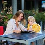有小女儿的年轻母亲有膳食在户外咖啡馆 免版税库存图片