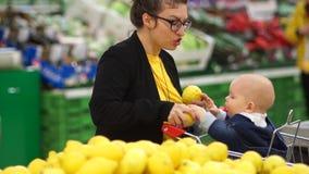 有小女儿购物的年轻母亲在超级市场 孩子拉扯在她的嘴,妇女的一个未洗的柠檬 股票视频