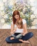 有小女孩和片剂个人计算机的愉快的母亲 免版税图库摄影