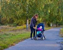有小女孩的妇女婴儿推车的 免版税库存照片