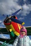 有小女孩的红色和黄色飞机 免版税库存图片