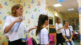 有小女孩的美发师 在理发沙龙的滑稽的孩子 有喷发剂的定象马尾辫 儿童理发店 影视素材