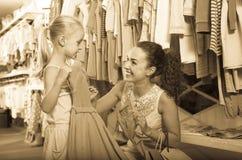 有小女孩的年轻感兴趣的妇女孩子服装精品店的 免版税图库摄影